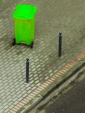 Plastic wheely bin in the street outside. Plastic green wheely bin in the street outside waiting for garbage truck. Top view Stock Photo