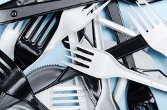 Plastic white and black forks and knives on a blue background. Concept plastic dishes, plastic pollution. Flat lay, top. View, texture stock photo