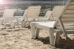 Plastic white chaise lounges on the empty beach of the riverbank Stock Image