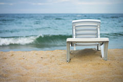 Plastic white lounge chair on empty beach. 