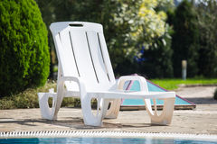 Plastic white sunbed near pool, Royalty Free Stock Images