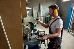 Plastic window and door manufacturing. Worker cutting PVC profile. And uses protective equipment stock photo