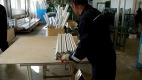 Plastic window and door manufacturing. Worker cutting PVC profile. Plastic window and door manufacturing. Worker cutting stock video footage