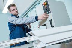 Plastic window and door manufacturing. Worker cutting PVC profile. Plastic window and door manufacturing. Production worker cutting PVC profile for double stock image