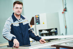 Plastic window and door manufacturing. Worker cutting PVC profile. Plastic window and door manufacturing. Production worker cutting PVC profile for double royalty free stock photo