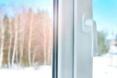 Home plastic window with a handle. Plastic window with a handle. Cold winter weather outside the window royalty free stock photos