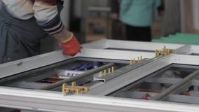 Plastic window production technology. Kyiv, Ukraine - June, 2017: The employee installs the accessories on the plastic window in the workshop of the workshop stock footage