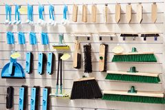 Plastic and wooden household brushes in hardware store. Plastic and wooden household brushes, scoops and mops in the hardware store Stock Photography