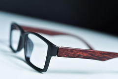 Plastic and wooden rimmed eyeglasses. Closeup of a pair of plastic and wooden rimmed eyeglasses on a white surface Stock Photography