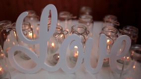Plastic word love on background candles stock video
