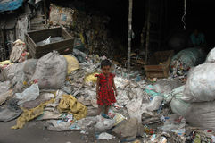 Plastic World. A little girl is standing in a heap of used plastic in a slum area of India Royalty Free Stock Photo