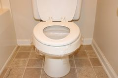 Plastic wrap on toilet seat April fools joke royalty free stock image