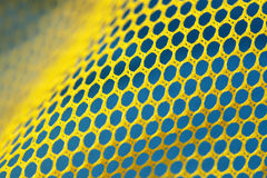 Plastic yellow net. Texture of a plastic yellow net over blue background Royalty Free Stock Photography