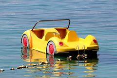 Plastic yellow paddle boat in shape of car floating on calm sea tied to shore with strong rope and multiple small white buoys. On warm sunny day royalty free stock photo