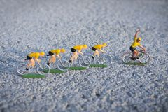 Plastic yellow road cyclists outdoor. Competition. Peloton. Plastic road cyclists. Yellow jerseys. Competition concept. Teamwork and leadership concepts royalty free stock photo