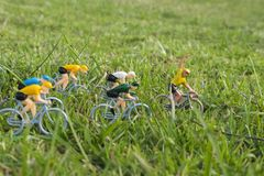 Plastic yellow road cyclists outdoor in the grass. Yellow jersey leadership. Competition. Peloton. Plastic road cyclists. Competition concept. Teamwork and royalty free stock photography