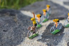 Plastic yellow road cyclists outdoor. V shape. Competition. Peloton. Plastic road cyclists. Yellow jerseys. Competition concept. Teamwork and leadership stock image