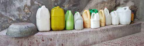 Plastic yellow, white and green jerricans for water and oil stand a long row on the concrete ledge gray wall, on left is an upturn. Plastic yellow, white and Royalty Free Stock Photography