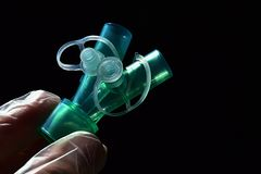 Plastic ypsilon piece of breathing system tubes connection with closed additional ports held in doctor lef hand in glove on dark Stock Images