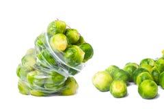 Plastic zak met bevroren die spruitjes op wit worden geïsoleerd veget Stock Foto's
