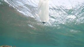 Plastic zak naast de ertsaders in het oceaan, onderwaterschot ecologische crisisfoto stock videobeelden