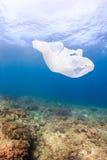 Plastic zak op een koraalrif Stock Foto's