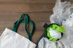 Plastic zakken in bak en canvastotalisatorzak op hout royalty-vrije stock afbeelding
