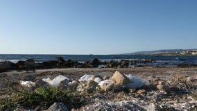 Plastic zakken en document afval op het zandige vuile strand Overzeese golven die het strand op de achtergrond raken stock video