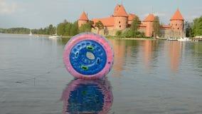 Plastic zorbing ball on lake water and Trakai castle. Plastic zorbing ball on the Galve lake water and Trakai castle stock video
