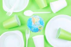 Plastica, inquinamento, ecologia, riciclante concetto Globo eliminabile di plastica della terra e delle stoviglie su fondo verde fotografia stock libera da diritti