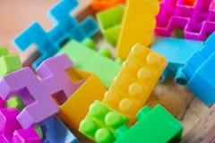 Plastica variopinta del giocattolo sul fondo di legno del pavimento Fotografie Stock