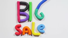 Plasticine big sale. Colorful letters made of plasticine appear in turns on white background and form combination big sale, shopping. Close up, stop motion, 4K stock footage
