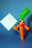 Plasticine carrot with poster. The funny plasticine carrot with poster on blue background Stock Image