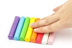 Plasticine colorido da haste da pressão de mão que arranja no backgro branco Foto de Stock Royalty Free