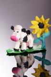 Plasticine cow with flower. On mirror Stock Photo