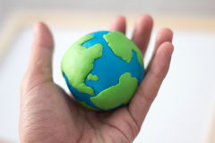 Plasticine globe in the hands , single focus. Plasticine globe symbolizing the land in the hands , single focus royalty free stock photos
