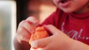 Plasticine hands of the baby play with modelling clay playdought.  stock footage