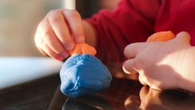 Plasticine hands of the baby play with modelling clay playdought Stock Photos