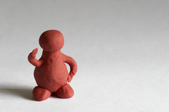 Plasticine man. With one hand up over grey background Royalty Free Stock Photography