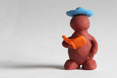 Plasticine man. Reading the book over grey background Royalty Free Stock Images