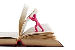 Plasticine man leafing through a book Royalty Free Stock Photos