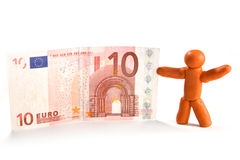 Plasticine man and money. Plasticine man standing and holding a banknote Stock Photography