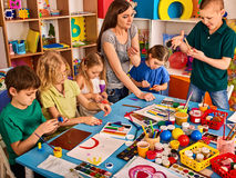 Plasticine modeling clay in children class. Teacher teaches in school. Plasticine modeling clay in children class. Teacher teaches kids together play dough and stock photos