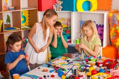 Plasticine modeling clay in children class. Teacher teaches in school. Plasticine modeling clay in children class. Teacher teaches kids together play dough and royalty free stock images