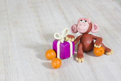 Plasticine monkey Christmas with a gift. Christmas monkey from plasticine hand made, A shot with place for the text Royalty Free Stock Photography