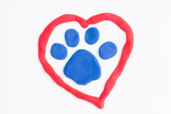 Plasticine paw and heart. Royalty Free Stock Images