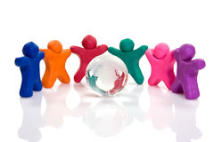 Plasticine people  surrounding a crystal globe Royalty Free Stock Photos