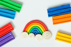 Plasticine rainbow with clouds and pieces of clay on white background stock photo