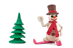 Plasticine skiing snowman. Standing near the Christmas tree   on white background Stock Photos