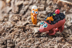 Plasticine small homemade hedgehog sitting on tree trunk. Royalty Free Stock Photography